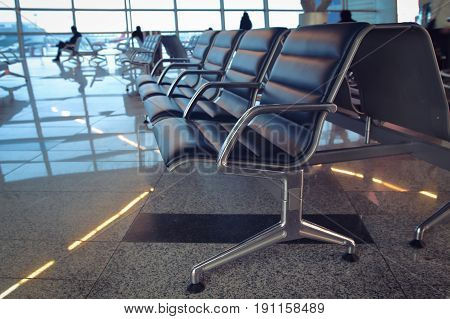 Seats in airport waiting room on background of silhouettes of passengers. Passengers are waiting for a flight to the plane at the airport.