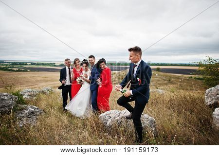 Groomsman Or Best Man Opening Up The Bottle Of Champagne In The Countryside With Wedding Couple And