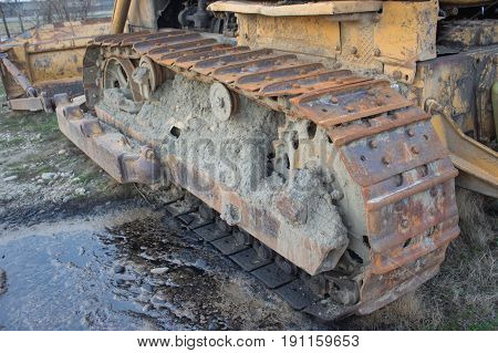 Continuous caterpillar tracks of the bulldozer. Old abandoned yellow bulldozer. Old rusty and weathered bulldozers