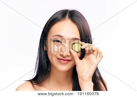 Cosmetic mask of cucumber for face, woman with cucumber on isolated background.