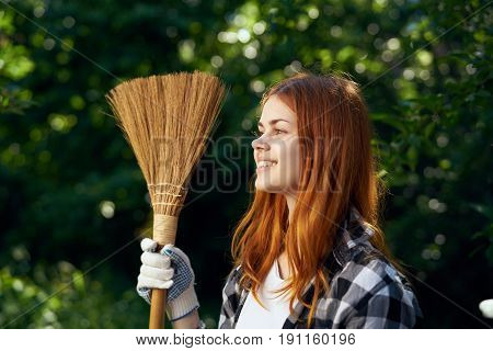 A woman with a broom in the country.