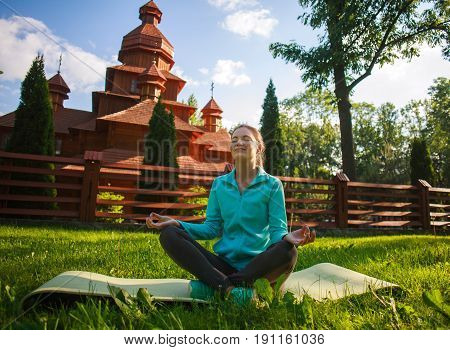 Young woman in summer park doing yoga with closed eyes