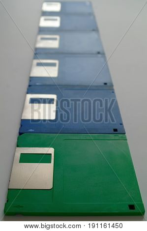 one green and blue 3.5 inch diskettes in a row