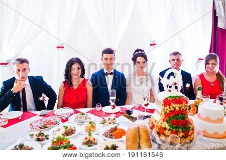 Wedding Couple And Bridesmaids With Groomsmen Sitting At A Table Full Of Tasty Dishes.