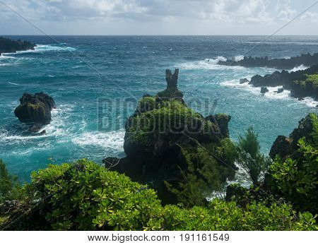 Vegetation covered rocks tower above the ocean at Waianapanapa State Park on the road to Hana in Maui, Hawaii