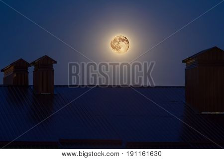 Full moon over the roof of house at night.