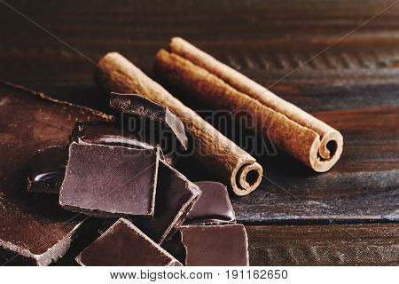 Pieces of bitter dark chocolate cubes and cinnamon stick on wooden background close-up view.