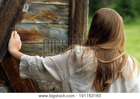 Young bohemian styled girl leaving a barn holding door open