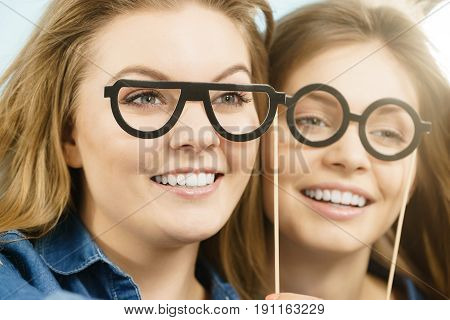 Two happy women holding fake eyeglasses on stick having fun wearing jeans shirts. Photo and carnival funny accessories concept.