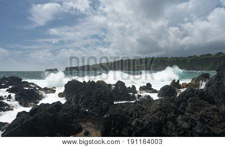 Black lava rocks line the shore at Keanae on the road to Hana in Maui, Hawaii
