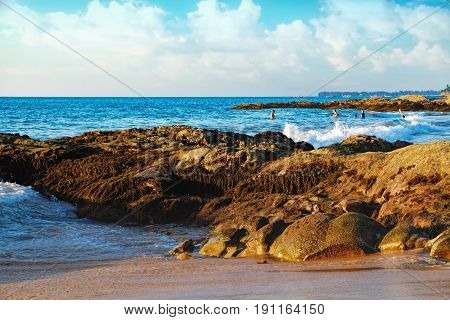 Beautiful seascape with sea and rock in Nang Thong Beach at sunset, Khao Lak, Thailand. View of calm sea with protruding grassy stones and vacationers. Selective focus
