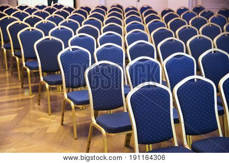 Empty conference chairs in row at a business room. Comfortable seats in empty corporate meeting office for presentation. Group of empty the same chairs with modern backrest and green upholstery in rows at unknown auditorium
