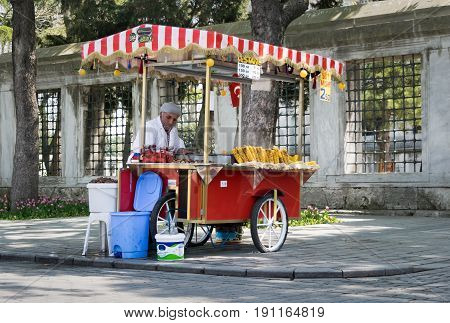 Istanbul Turkey - April 16 2017: Old man selling chestnut and corn on traditional Turkish fast food cart in Sultan Ahmed Square