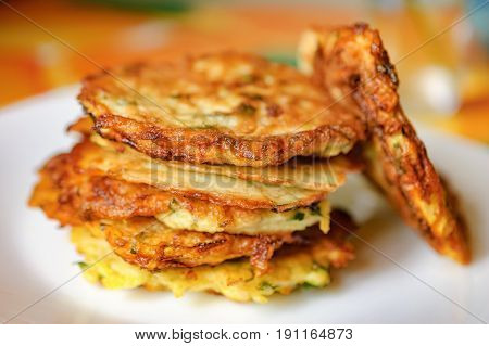 Stack of fried vegetable fritter made of zucchini eggs parsley decorated with a sprig of green onions on a white plate. Selective Focus focus on the front of the top fritters