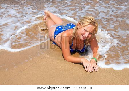 girl on the sand in the wave of the sea