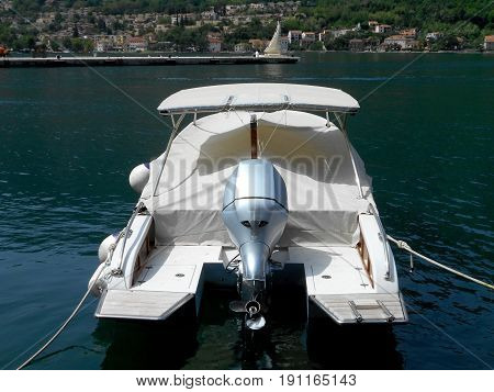 White speedboat, covered with a protective canvas, moored to the dock