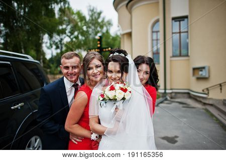 Charming Bride With A Groomsman And Bridesmaids Standing Outside The Church Next To The Luxurious We