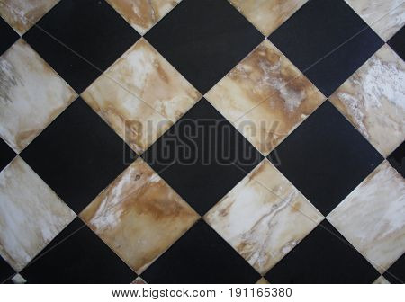 Checker board pattern of black and white marble squares that are very old and hand cut.