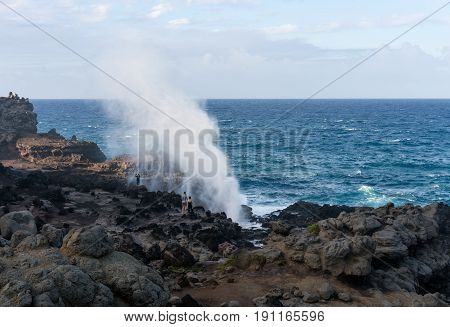 Famous Nakalele blowhole on north coast of Maui erupts as strong waves crash against the lava shoreline in Hawaii