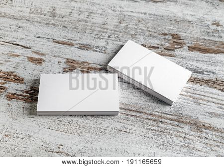 Photo of blank business cards on vintage wood table background. Presentation template for branding identity.
