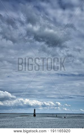 Little lighthouse in the sea, cloudy sky and copyspace available
