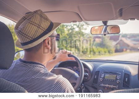 Young driver driving a car with his hands on the steering wheel