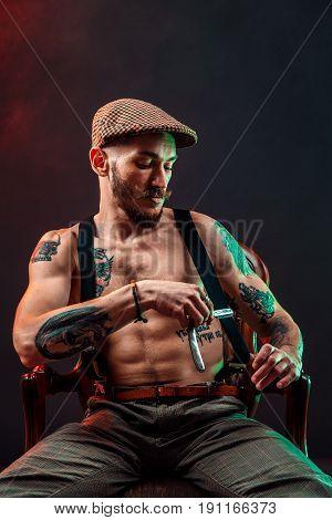 Stylish tattooed shirtless barber gangsta man with razor looking at camera.