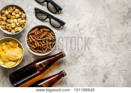 home party with TV watching, snacks, pop corn, chips and bread crumbs and beer on stone background top view mock up