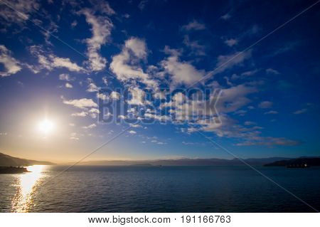 SOUTH ISLAND, NEW ZEALAND- MAY 25, 2017: Beautiful sunset in the horizont, looking from Ferry that provide daily connection between North and South islands with a beautiful blue sky located in New Zealand.