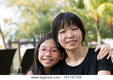 Portrait of Asian loving mother with her daughter outdoor
