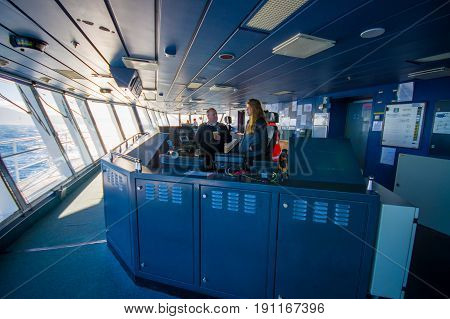 SOUTH ISLAND, NEW ZEALAND- MAY 25, 2017: Ferry boat pilot command cabin with the captain operating the machines with a beautiful assistant looking a beautiful view on the sea, in new zealand.