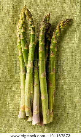 Bundle of fresh cut raw uncooked green asparagus vegetable on green cloth background