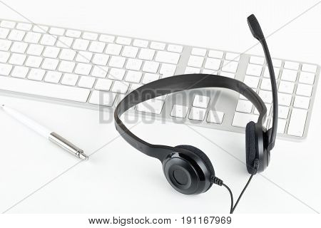 Computer headset with microphone on computer keyboard on white table - communication or helpcenter concept