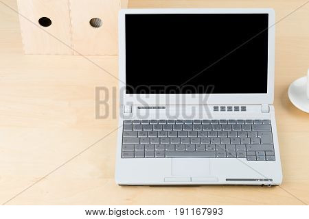 Brown wooden office desk with cup folders and laptop with empty screen copy space