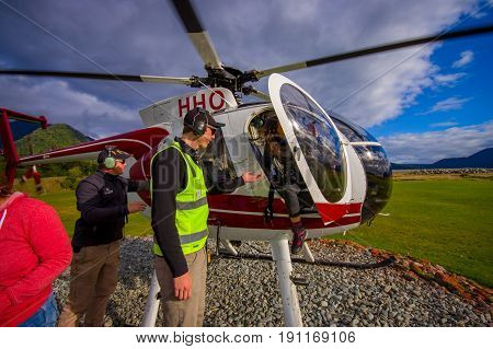 SOUTH ISLAND, NEW ZEALAND- MAY 25, 2017: An unidentified passenger alight from a helicopteter onto the snow above Franz Josef Glacier, Westland, New Zealand.