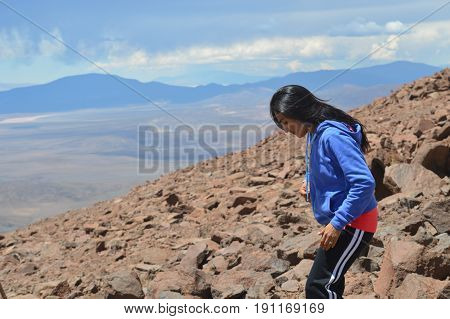 Young woman explores the heights of Acay in Salta, Argentina