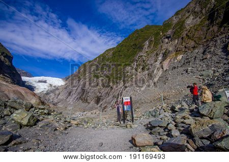 SOUTH ISLAND, NEW ZEALAND- MAY 25, 2017: Unidentified people hiking the Franz Josef Glacier and valley floor, Westland, South Island, New Zealand.