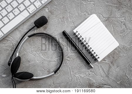 operator headset, notebook and keyboard for contact us feed back on call center workdesk stone background top view mockup