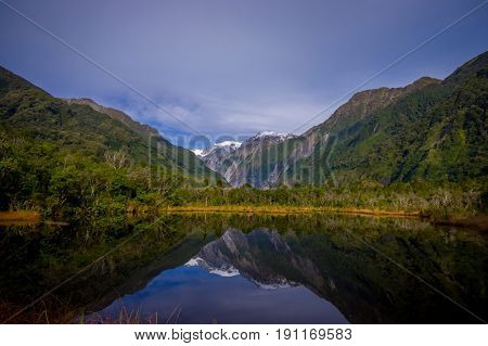 Small pond peters pond with reflection of mountain glacier Franz Josef Glacier in New Zealand.