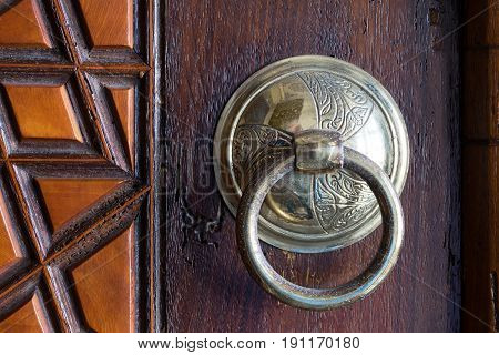 Closeup of antique copper ornate door knocker over an aged wooden door Suleymaniye Mosque Istanbul Turkey