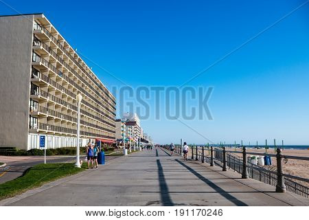 VIRGINIA BEACH, VIRGINIA - AUGUST 9, 2015:  People exercise in the early morning on the Virginia Beach Boardwalk, a popular resort in the Hampton Roads area, which stretches 3 miles long.