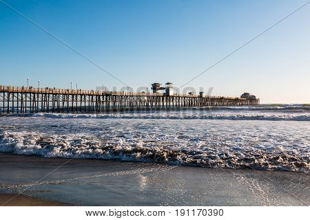 OCEANSIDE, CALIFORNIA - MARCH 23, 2017:  Waves crash on the beach with the historic Oceanside fishing pier in the background, billed as the longest wooden over-water pier on the west coast.