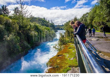 A crown of people over the bridge enjoying the view of the powerful Huka Falls on the Waikato River near Taupo North Island New Zealand.