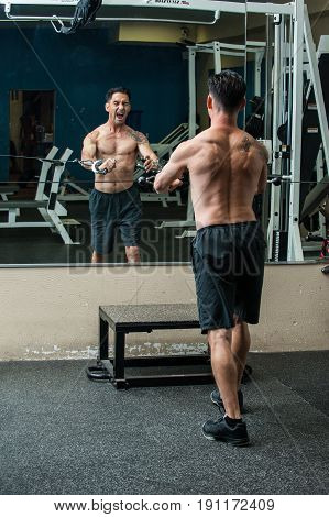 Middle age muscular man performing cable chest press exercise with face and torso reflected in mirror and intense expression.