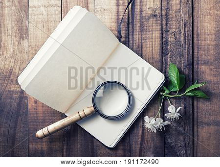 Still life with a notepad. Blank opened notebook magnifier cherry flowers and green leaves on vintage wood background. Stationery elements. Responsive design mockup.