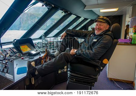 SOUTH ISLAND, NEW ZEALAND- MAY 25, 2017: Close up of a ferry boat pilot command cabin with a smiling captain holding a cup of coffe with thumps up, in new zealand.