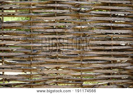 A self-made garden fence made of intertwined branches.