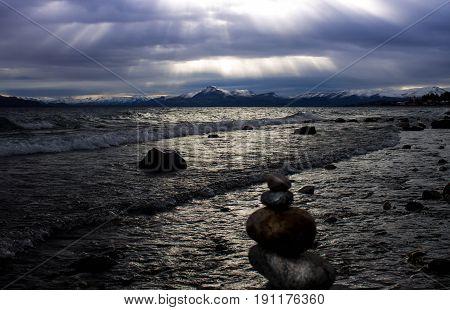 Sunset on the rocky coast of nahuel hiapi lake in patagonia.