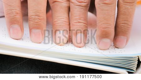 Fingers Of Blind Man Touching Page On Braille Book