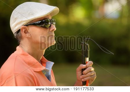Portrait Of Blind Man Sitting In City Park